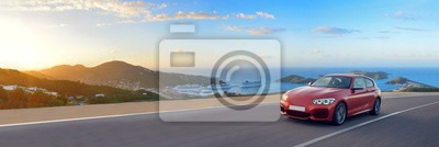 Image of Fototapeta red sports car driving on a long mediterranean road